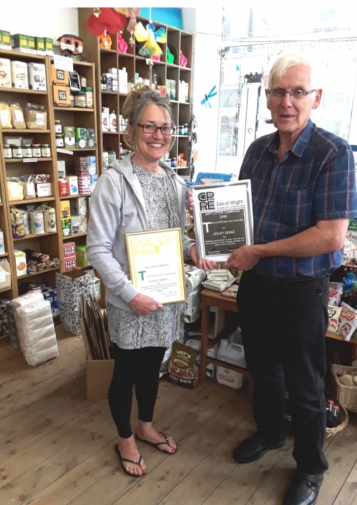 Lesley in her shop with her old and new certificates
